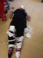 Volunteer wrapped up in bandages during a first aid course